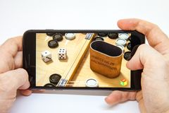 Mosca/Russia - 19 febbraio 2019: smartphone a disposizione download del gioco della tavola reale fotografia stock libera da diritti