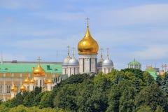Mosca, Russia - 21 giugno 2018: Cupole dorate delle cattedrali nel Cremlino di Mosca contro gli alberi ed il cielo blu verdi immagine stock