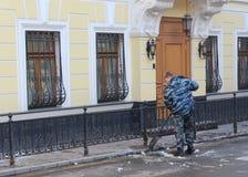 Mosca, Russia, il 24 marzo 2018, uomo di A, vestito in vestiario di protezione, rimuove il resti di neve Immagini Stock Libere da Diritti
