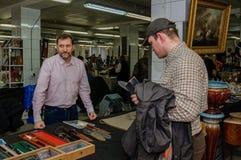 Mosca, Russia - 19 marzo 2017: Venditore dei coltelli, dei pugnali e delle pistole antichi dietro il contatore con un'arma Fotografie Stock