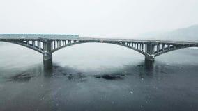 Mosca sobre el puente Tren de la ciudad que se mueve a través del puente el invierno Tren de la ciudad que se mueve a través del  metrajes