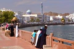 MOSCATEL, OMÁN - 10 DE FEBRERO DE 2012: Corniche de Muttrah en Muscat con los muchachos jovenes omaníes vestidos tradicionalmente Imágenes de archivo libres de regalías