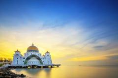 Moschee durch das Meer während des Sonnenaufgangs mit buntem Himmel stockfoto