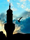 Moscheenturmschattenbild über dem blauen Himmel auf Dämmerung und einem Vogel Stockfotografie