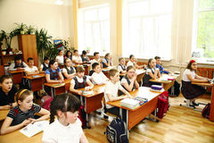 Moscou, estudante de Rússia-agosto 16,2016-Little que senta-se atrás da mesa da escola Imagens de Stock Royalty Free