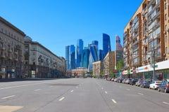 MOSCOU, MAIO, 9, 2018: A opinião de perspectiva da estrada do carro da cidade entre construções e as lojas com o escritório para  imagem de stock royalty free