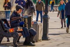 MOSCOU, RÚSSIA ABRIL, 24, 2018: Opinião exterior homem não identificado que senta-se em uma cadeira pública e que joga o acordeão imagem de stock