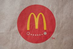 Moscou, Rússia - 6 de abril de 2019: Entrega do alimento do logotipo de mcdonald no fundo marrom do papel do ofício Close-up Vist fotos de stock