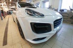 Moscou, Rússia - 19 de abril de 2019: Porsche Cayenne branco no jogo largo do corpo do magnum de TechArt Suportes no centro de se foto de stock