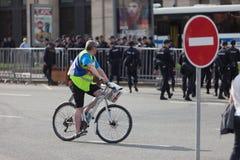 MOSCOU, RÚSSIA - 30 DE ABRIL DE 2018: Um homem em uma bicicleta que carrega o ` do ` H do logotipo o logotipo de Navalny após a r Imagens de Stock