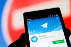 MOSCOU, RÚSSIA - 17 DE ABRIL DE 2018: Um telefone celular na mão com a aplicação do telegrama na loja do jogo de Google fotografia de stock royalty free