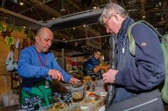 Moscou, Rússia - 25 de fevereiro de 2017: O vendedor de cogumelos conservados produzidos casa na feira põe em um frasco para o co Imagens de Stock