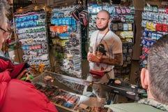 Moscou, Rússia - 25 de fevereiro de 2017: Vendedor no fundo do contador com linhas e engrenagem de pesca Fotografia de Stock