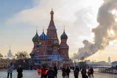 Moscou, Rússia - 14 de fevereiro de 2018: Turistas de passeio no quadrado vermelho contra a catedral do ` s da manjericão do St fotos de stock royalty free