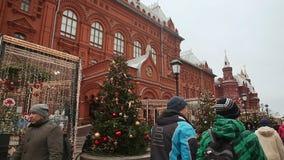 MOSCOU, RÚSSIA - 1º DE JANEIRO DE 2017: Transeuntes de passeio no mercado do Natal no quadrado vermelho As árvores de Natal verde filme