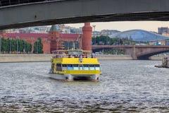 Moscou, Rússia - 19 de junho de 2018: Barco de prazer que flutua sob a ponte sobre o rio de Moskva em um fundo do Kremlin de Mosc Fotos de Stock