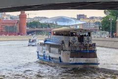 Moscou, Rússia - 19 de junho de 2018: Barco de prazer que flutua sob a ponte sobre o rio de Moskva em uma noite nebulosa do verão Imagens de Stock Royalty Free