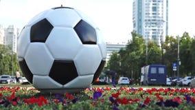 Moscou, Rússia - 26 de junho de 2018 Escultura de uma bola do futebol em uma rua de Moscou com condução de carros no fundo filme