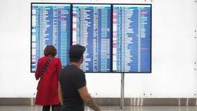 Moscou, Rússia - 6 de maio de 2019: Espera da mulher para a partida no aeroporto, placa da partida, calendário eletrônico do aero video estoque