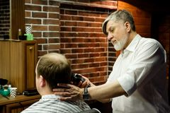 MOSCOU, RÚSSIA - 24 DE MAIO DE 2018: O barbeiro Sergei Urazov do russo faz Fotografia de Stock Royalty Free
