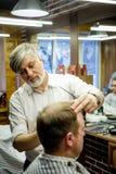 MOSCOU, RÚSSIA - 24 DE MAIO DE 2018: O barbeiro Sergei Urazov do russo faz Fotos de Stock Royalty Free