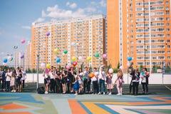 Moscou, Rússia - 22 de maio de 2019: Os graduados da escola estão na jarda e deixam os balões imagens de stock