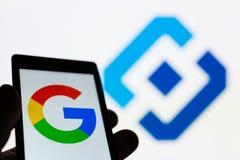 MOSCOU, RÚSSIA - 9 DE MAIO DE 2018: Smartphone à disposição com logotipo de Google Emblema de Roskomnadzor RKN no fundo imagens de stock royalty free