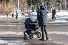 MOSCOU, RÚSSIA - 2 DE MARÇO DE 2019: Único homem com carrinho de criança de bebê, caminhadas do transporte no parque do inverno imagem de stock