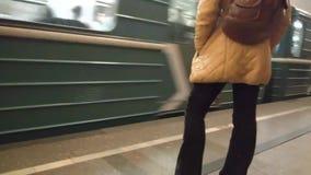 MOSCOU, RÚSSIA - 16 DE SETEMBRO DE 2018: Mulher, na calças, em um revestimento alaranjado, com uma trouxa no fundo da chegada de vídeos de arquivo