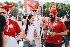 MOSCOU, RÚSSIA - EM JUNHO DE 2018: Fãs dinamarqueses que vestem os capacetes de Viking pintados em cores nacionais com uma menina fotos de stock