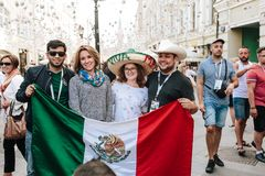 MOSCOU, RÚSSIA - EM JUNHO DE 2018: Os fãs de México são fotografados com as meninas do russo com a bandeira do país e na foto de stock