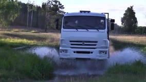 Moscou, Rússia - em setembro de 2018: Veículos do frete que viajam na estrada secundária com poças cena O caminhão monta em empoe vídeos de arquivo