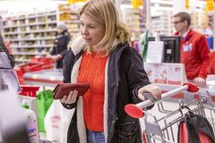Moscou, Rússia, 11/22/2018 A jovem mulher que paga por compras em checkout foto de stock royalty free