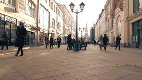 MOSCOU, RÚSSIA - MARÇO, 12, 2017 Os turistas andam ao longo da rua de Nikolskaya perto do quadrado vermelho e do Kremlin distante Imagens de Stock Royalty Free