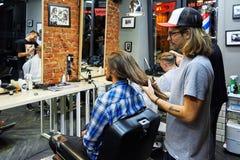 Moscou, Rússia, 06 05 2018: um homem sério que olha à câmera quando seu cabelo longo for eliminado para um fundraiser do câncer imagens de stock