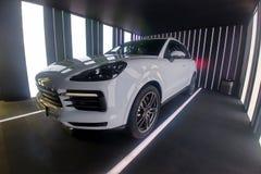 Moscou, R?ssia - 9 de maio de 2019: Porsche Cayenne branco completamente novo em uma caixa de apresenta??o A parte dianteira e a  imagens de stock royalty free