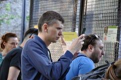 Moscou, R?ssia - 25 de maio de 2019: uma multid?o de povos para tomar imagens e disparar no v?deo dos dispositivos dos telefones  foto de stock
