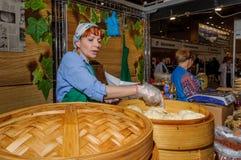 Moscou, Russie - 25 février 2017 : La femme prépare le pyan-Se coréen national d'aliments de préparation rapide dans un vapeur en Photographie stock