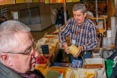 Moscou, Russie - 25 février 2017 : Le vendeur aux cheveux gris d'homme à la foire remplit pot du miel pour l'acheteur Images libres de droits