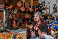 Moscou, Russie - 25 février 2017 : Vendeuse des souvenirs et de l'artisanat indigènes en prévision des acheteurs Image libre de droits