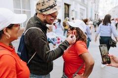 MOSCOU, RUSSIE - JUIN 2018 : Un homme dessine le drapeau du Pérou sur le visage d'une femme habillée dans un T-shirt rouge photographie stock