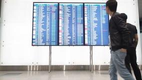 Moscou, Russie - 6 mai 2019 : Les gens attendent le départ dans l'aéroport, panneau de départ, horaire électronique d'aéroport banque de vidéos