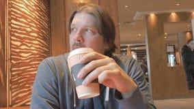 Moscou, Russie - 16 mars 2019 : Homme dans la tenue de détente buvant lentement du café de la tasse de papier chez mcdonald Type  banque de vidéos
