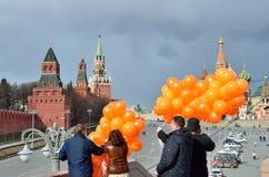Moscou, Russie, mars, 20, 2016, scène russe : les gens avec les ballons oranges devant la cathédrale du ` s de St Basil à Moscou Photographie stock