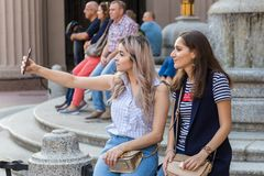 Young girls sit on a bench and make selfies on a smartphone royalty free stock image
