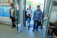 MOSCOW, AUG.29, 2018: View on group of people coming into the passenger train through automatic doors. People traveling on city ex stock images