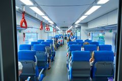 MOSCOW, AUG.29, 2018: View on seating and standing people and bikes in a special parking holder in new modern passenger train salo royalty free stock images