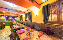 MOSCOW - AUGUST 2014: Interior of the Mexican nightclub restaurant. `SOMBRERO`. Hall with a restaurant with wooden furniture. Row of tables with couches near stock image