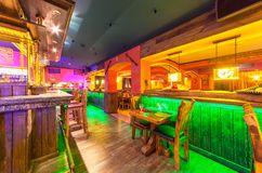 MOSCOW - AUGUST 2014: Interior of the Mexican nightclub restaurant. `SOMBRERO`. Separate wooden table near the bar with a green backlight royalty free stock photography