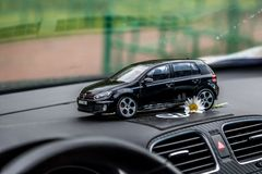 Moscow. Autumn 2018. Black toy car stays on dashboard of the same real car. Volkswagen golf 6, logo mat vw